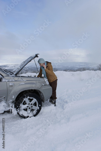 Woman standing in snow checking underneath carճ hood talking on cell phone