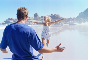 Man with arms outstretched greeting arriving girlfriend on beach