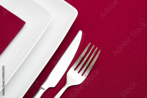 Red tablecloth with white square plates and red napkin