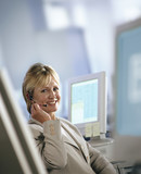 Smiling businesswoman in headset sitting at desk