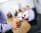Business people watching co-worker giving presentation holding red marker