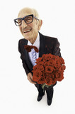 Smiling senior man in tuxedo holding bouquet of red roses