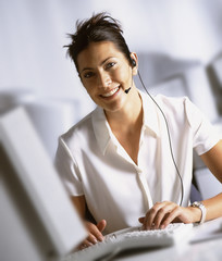 Smiling businesswoman in headset typing on computer