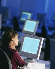 Businesswoman sitting at desk working late and rubbing neck