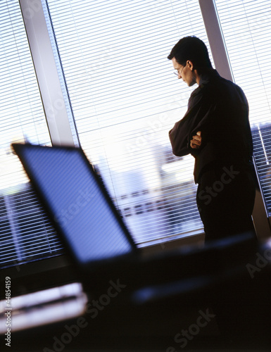 Businessman with arms crossed looking out office window
