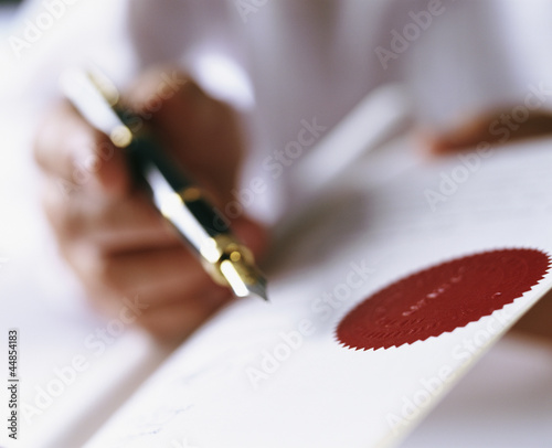 Close up of businessman holding fountain pen and paper with red seal