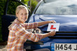 Portrait of smiling young woman attaching learnerճ permit sticker to car
