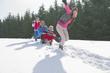 Happy family sledding in snow