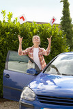 Smiling young woman throwing learnerճ permit sticker in air next to car