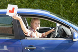 Portrait of smiling young woman driving car and throwing learnerճ permit sticker out window