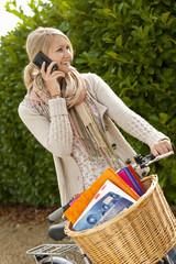 Smiling young woman talking on cell phone on bicycle with textbooks in basket
