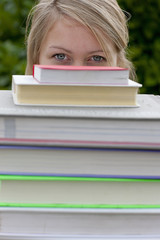 Close up of young woman peering from behind stack of textbooks