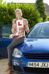 Portrait of smiling young woman holding learnerճ permit sticker on hood of car