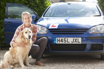 Portrait of smiling young woman with dog in front of car with learnerճ permit