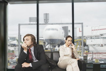 Serious businessman and businesswoman waiting in airport