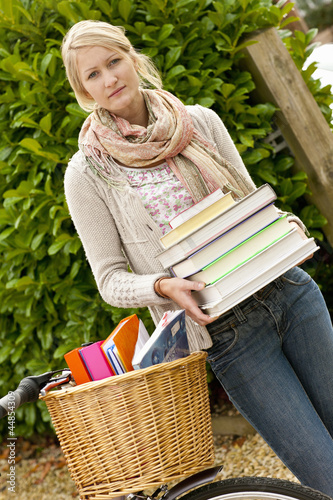 Portrait of young woman holding textbooks next to bicycle with basket