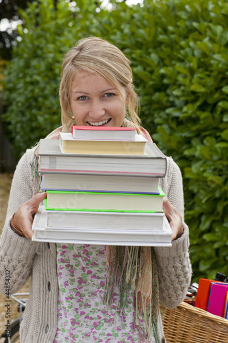 Portrait of smiling young woman holding stack of textbooks