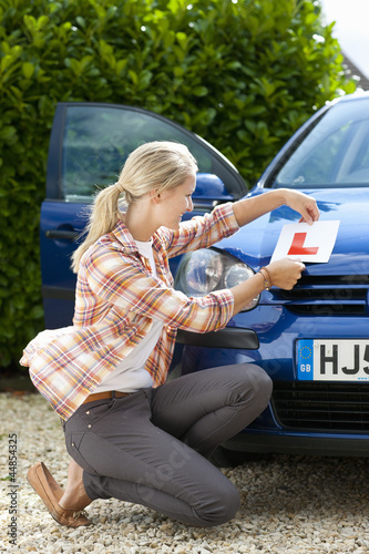 Young woman attaching learnerճ permit sticker sticker to hood of car