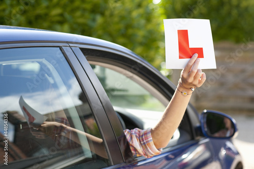 Young woman holding learnerճ permit sticker