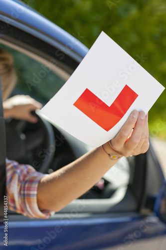 Close up of young woman holding learnerճ permit sticker