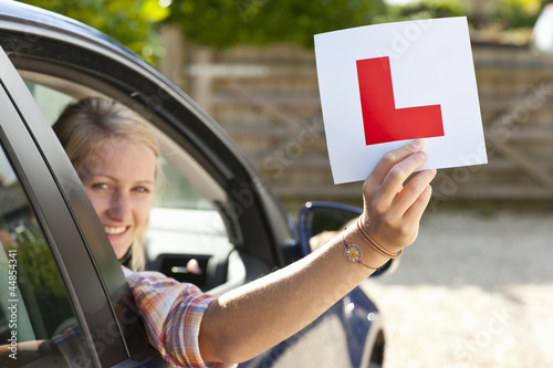 Portrait of smiling young woman driving car and holding learnerճ permit sticker out window