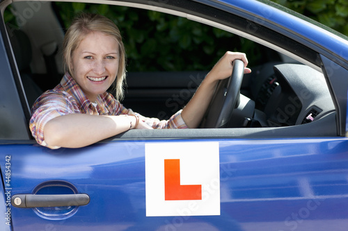 Portrait of smiling young woman driving car with learnerճ permit sticker