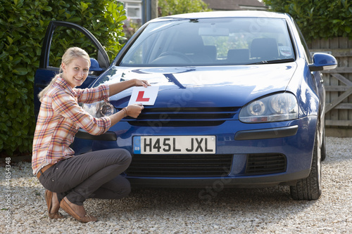 Portrait of smiling young woman attaching learnerճ permit sticker to hood of car