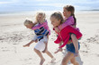 Kids running and piggybacking on sunny beach