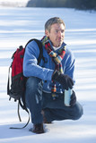 Man crouching in snow with backpack and insulated drink container