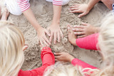 Hands of kids making sandcastle on beach