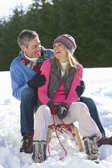 Laughing couple sitting on sled in snow