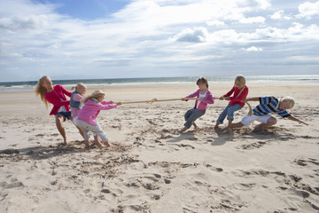Kids playing tug-of-war on sunny beach