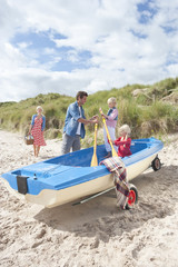 Family with paddles and boat on beach