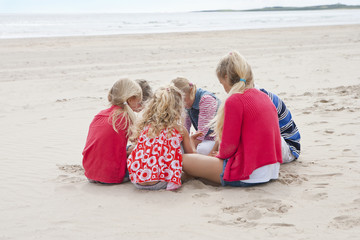 Kids sitting in circle on beach