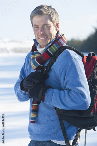 Portrait of smiling man with backpack in snow