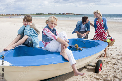 Happy family in boat on beach