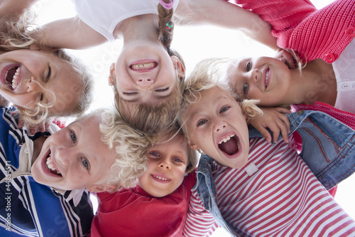 Portrait of exuberant kids in huddle