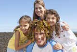 Family hugging man with seaweed on head