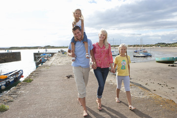 Portrait of smiling family walking along harbor