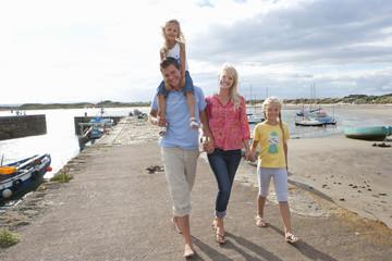 Portrait of smiling family walking along harbor
