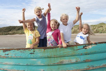 Portrait of enthusiastic boy and girls with arms raised in boat on beach
