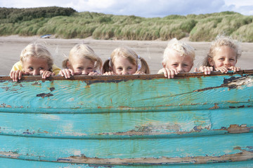 Portrait of smiling boy and girls peering from behind boat on beach