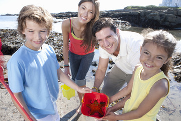 Portrait of smiling family holding pail with starfish on sunny beach