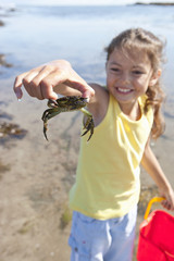 Smiling girl holding small crab on sunny beach