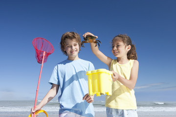Boy and girl holding crab on sunny beach