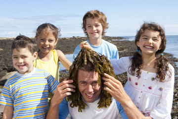 Portrait of smiling kids holding seaweed over man's head on sunny beach