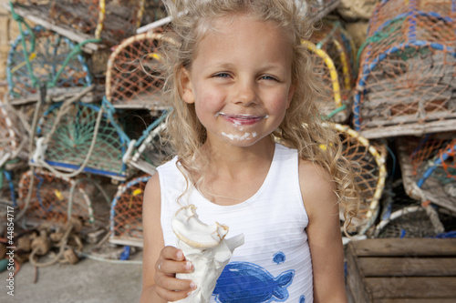 Portrait of smiling girl with ice cream on face in front of lobster traps