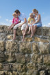 Barefoot family sitting on stone wall