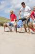 Man and kids playing wheelbarrow race on sunny beach