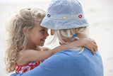 Mother and daughter hugging face to face on beach